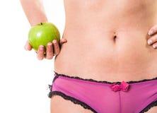 Frau mit perfektem Körper und Apfel in der Hand Stockfotografie