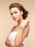 Frau mit Perlenohrringen und -armband Stockfotografie