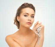 Frau mit Perlenohrringen und -halskette Stockbilder