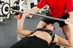 Frau mit persönlichem Kursleiter in der Gymnastik Lizenzfreie Stockbilder
