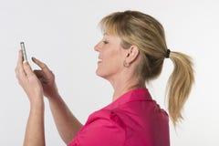 Frau mit Pferdeschwanz unter Verwendung eines Telefons Stockfotografie