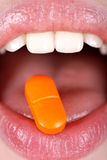 Frau mit Pille auf Zunge Stockbilder