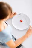 Frau mit Platte und einer Tomate Stockbild