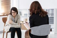 Frau mit Problem und Unterst?tzungsratgeber w?hrend der Therapie-Sitzung stockfoto