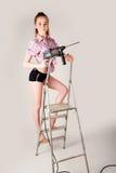 Frau mit Puncher auf Leiter Stockbilder