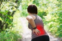 Frau mit Rückenschmerzen, Nierenentzündung, Verletzung während des Trainings stockbilder