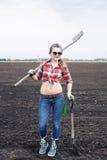 Frau mit Rührstange und Schaufel auf Feld Lizenzfreies Stockfoto