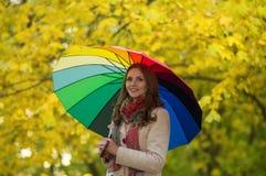 Frau mit Regenbogenregenschirm Stockfotografie