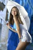 Frau mit Regenschirm auf einer Straße und einem hellen Regen lizenzfreie stockfotos