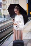 Frau mit Regenschirm an der Bahnstation, die Telefon betrachtet Lizenzfreie Stockfotografie