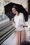 Frau mit Regenschirm an der Bahnstation, die Telefon hält Lizenzfreie Stockfotos