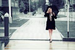 Frau mit Regenschirm im Regen Stockbild