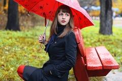 Frau mit Regenschirm im Park Stockfotos
