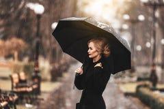 Frau mit Regenschirm im Regen Stockfotos
