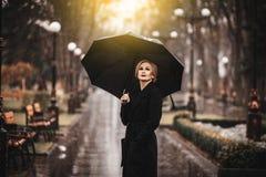 Frau mit Regenschirm im Regen Lizenzfreie Stockfotos