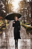 Frau mit Regenschirm im Regen Stockfotografie