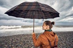 Frau mit Regenschirm nahe stürmischem Meer Stockfoto