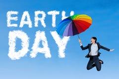 Frau mit Regenschirm und Tag der Erde-Text Lizenzfreie Stockbilder