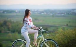 Frau mit Retro- Fahrrad auf dem Hügel am Abend Lizenzfreie Stockfotografie