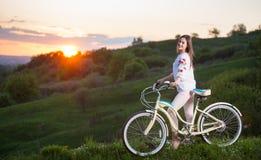 Frau mit Retro- Fahrrad auf dem Hügel am Abend Stockfotos