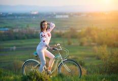 Frau mit Retro- Fahrrad auf dem Hügel am Abend Stockbilder
