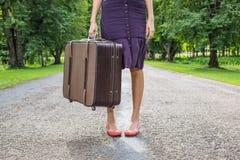 Frau mit Retro- Weinlesegepäck auf leerer Straße Stockfoto