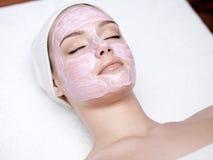 Frau mit rosafarbener Gesichtsschablone lizenzfreie stockfotos