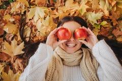 Frau mit rotem Apfel im Herbstpark Jahreszeit-, Frucht- und Leutekonzept - schönes Mädchen, das auf dem Boden und Herbstlaub lieg lizenzfreies stockbild
