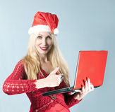 Frau mit rotem Laptop zeigt einen Daumen Stockfotos