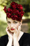 Frau mit rotem Lippenstift und Blumen auf dem Kopf Lizenzfreie Stockfotos