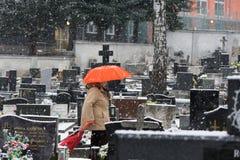 Frau mit rotem Regenschirm auf einem Kirchhof bedeckt durch Schnee im Winter lizenzfreies stockfoto