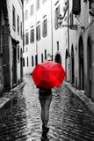 Frau mit rotem Regenschirm auf Retro- Straße in der alten Stadt Wind und Regen stockfotografie