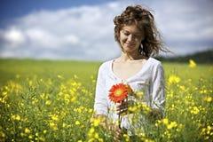 Frau mit roten Blumen auf dem Rapssamengebiet. Lizenzfreie Stockfotografie