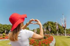 Frau mit roten Hutrahmenblumen in Herzform, Fingerherzrahmen, Ansicht betrachtend lizenzfreies stockbild