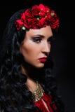 Frau mit roten Rosen in ihrem Haar Lizenzfreie Stockbilder