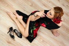 Frau mit roter Blume im schwarzen Kleid mit Schuhen Lizenzfreies Stockbild