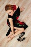 Frau mit roter Blume im schwarzen Kleid mit Schuhen Stockbild