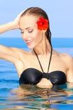 Frau mit roter Blume im Swimmingpool Lizenzfreie Stockfotografie