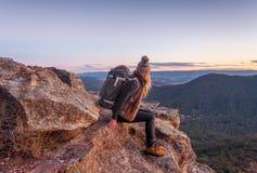 Frau mit Rucksack auf Bergspitze Blau-Bergen lizenzfreie stockfotografie