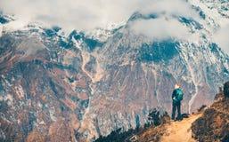 Frau mit Rucksack auf dem Weg und den Bergen Stockfoto
