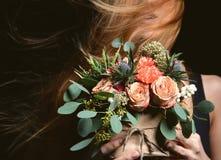 Frau mit rustikalem Blumenstrauß der Weinlese der wilden Rosen Gartennelkenblume Stockfotos