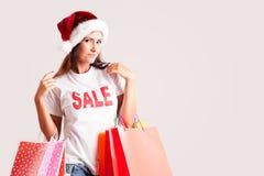 Frau mit Sankt-Hut und -Einkaufstaschen Stockfotos