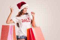 Frau mit Sankt-Hut und -Einkaufstaschen Lizenzfreies Stockfoto
