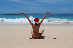 Frau mit Sankt-` s Hut auf einem tropischen Strand Lizenzfreie Stockfotografie