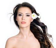 Frau mit sauberer Haut und Blumen in ihrem langen Haar Lizenzfreies Stockfoto