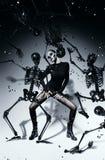 Frau mit Schädelgesichtstanzen mit den schwarzen Skeletten Stockfotografie