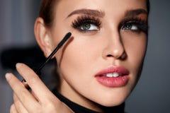 Frau mit Schönheits-Make-up, lange schwarze Wimpern, die Wimperntusche anwenden stockbild
