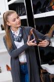 Frau mit Schuh wählt in der Hand auf den Fersen gefolgte Schuhe Stockbild