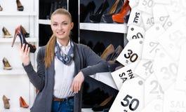 Frau mit Schuh wählt in der Hand stilvolle Pumpen im Verkauf lizenzfreie stockbilder