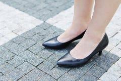 Frau mit Schuhen auf Pflastersteinen Stockfotografie